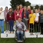 Paraolimpietis Aigars Apinis kopā ar uzvarētājām 4x100 m stafetē 6. - 7.klašu grupā: Ikšķiles vidusskolas (no kreisās), Lēdmanes pamatskolas un Ogres 1.vidusskolas jaunajām sprinterēm.