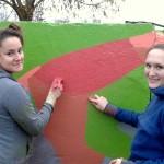 Ogres Interakta kluba pārstāves (no kreisās) Diāna Mikāne un Ausma Graudiņa darba procesā – rūpīgi un ar mīlestību top zīmējums uz Ogres stadiona sienas dzelzceļa pusē.